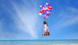 dream concept, girl flying on multicolored balloons in blue sky, imagination and creativity
