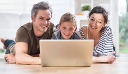 At home, cheerful family sharing a funny video on a laptop